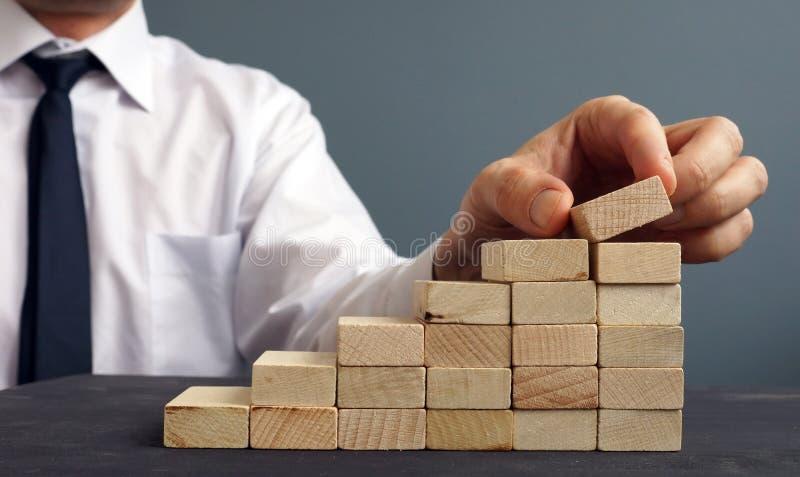 Succes in zaken en carrière De mens neemt beeldje op een ladder van houten blokken toe royalty-vrije stock afbeeldingen