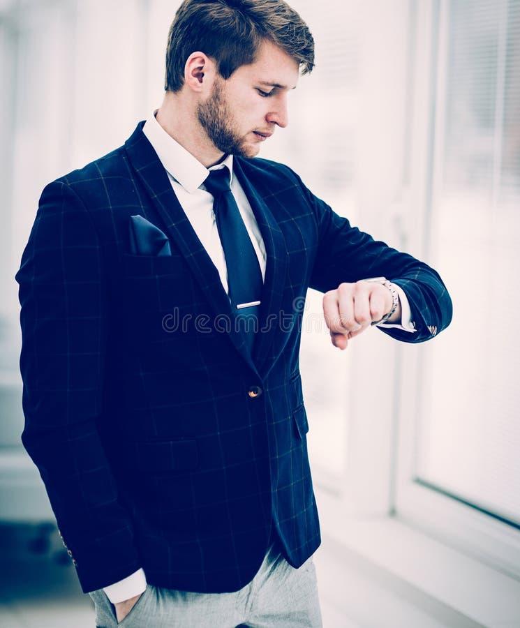 Succesconcept in zaken - een beginnerszakenman bekijkt zijn horloge stock foto's