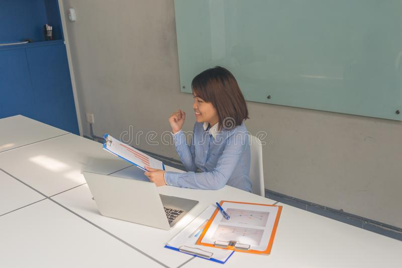 Succesful Asian businesswoman reading financial reports and feel happy stock photo