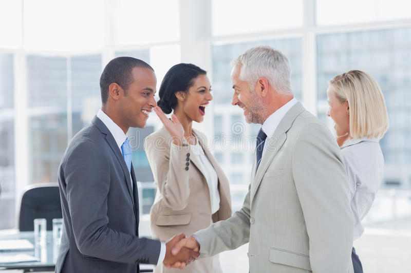 Succesful business team shaking hands and high fiving stock images