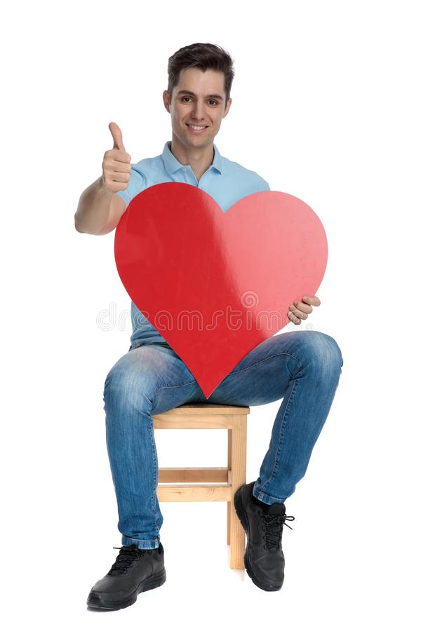 Succesful casual guy holding a heart shape and gesturing ok. While smiling and wearing jeans, sitting on a chair on white studio background royalty free stock photography