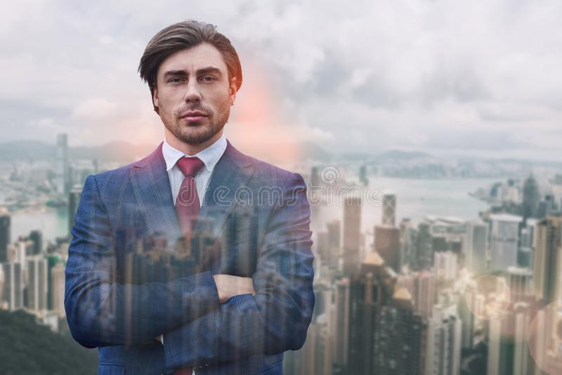 Succesful and rich. Close-up portrait of attractive man in suit keeping his arms crossed while standing against of stock images