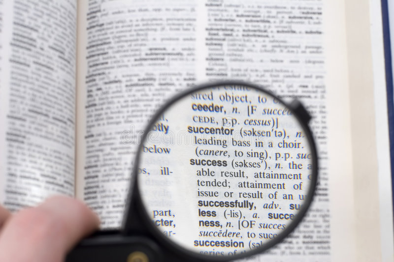 Success. A dictionary with the word success highlighted with a magnifying glass stock photography