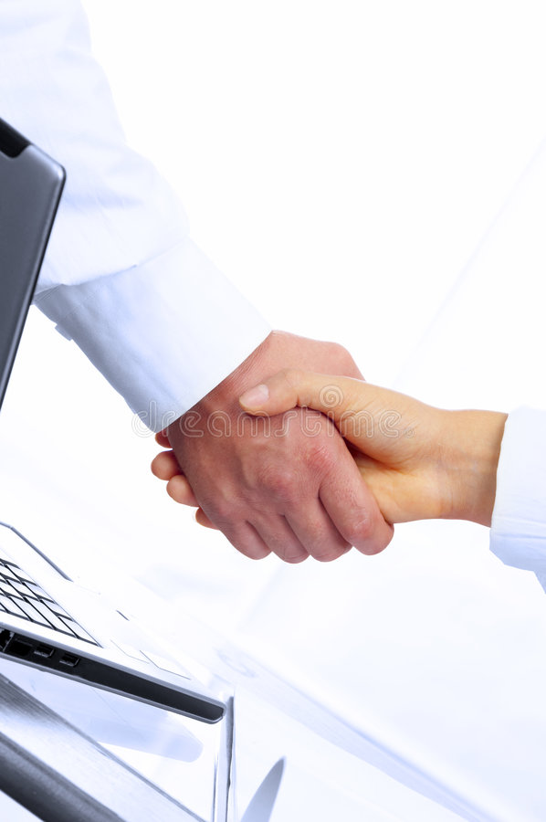 Success. View of handshake over paper and computer in the background stock photo