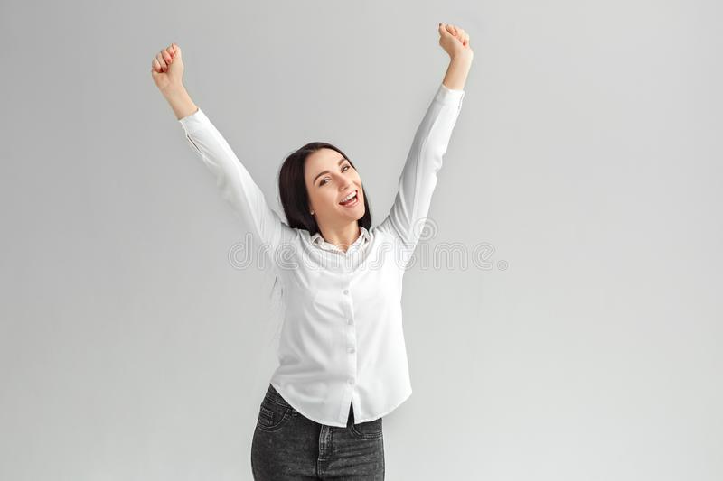Success Achieved. Woman standing isolated on gray hands up shouting cheerful royalty free stock photos