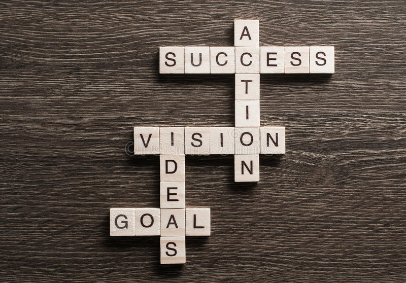 Success achieving business keywords collected of wooden cubes in crossword stock image