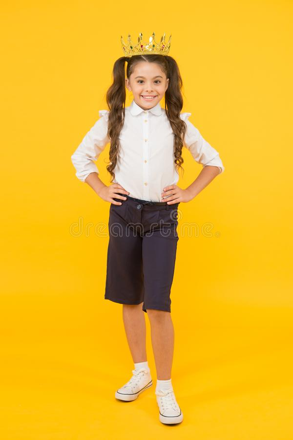 Success attends hard work. Happy girl enjoying success on yellow background. Little schoolchild being excited about royalty free stock photography