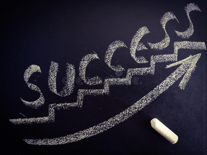 Success bricks with growing graph on chalkboard concept stock photo