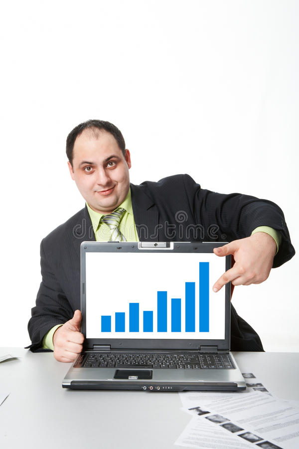 Success in business. Photo of middle aged employer showing thumb up while pointing at chart on laptop screen stock photo