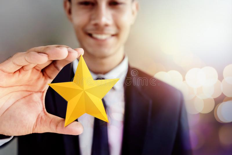 Success in Business or Personal Talent Concept. Happy Businessman in black suit Smiling and Showing a Golden Star in Hand stock images