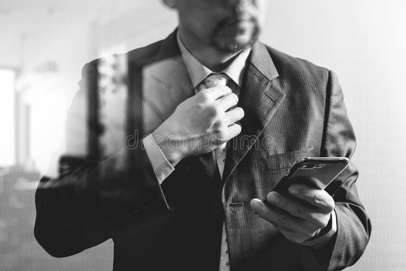 success businessman holding tie and using smart phone,thinking,front view,filter effect,omni channel,black and white stock photo