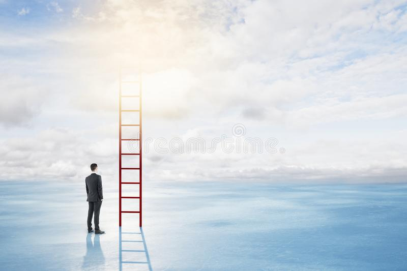 Success and career development concept. Thoughtful young businessman climbing ladder on bright sky with clouds background. Success and career development concept royalty free stock photos
