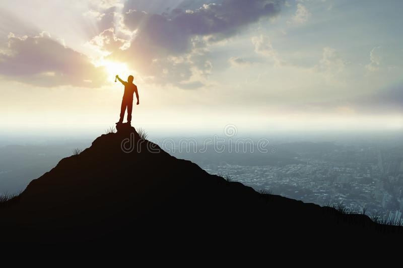 Success or champion man on mountain holding winner& x27;s Golden. Medal, concept as improving, faith and believe of successful man in sport, finance, business stock photos