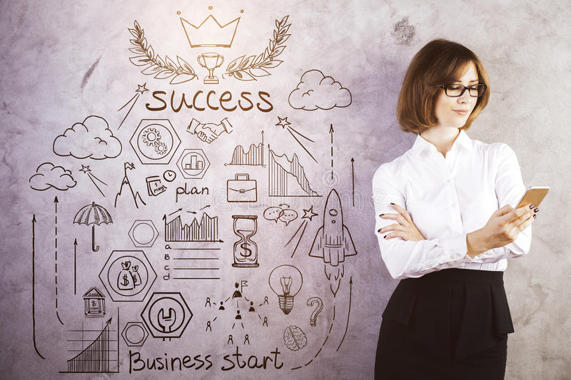 Success concept. Attractive young woman using smartphone on concrete background with business sketch. Success concept stock photo