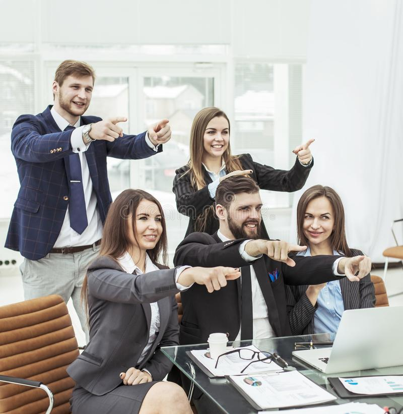 Success concept in business - friendly business team showing forefinger forward royalty free stock image