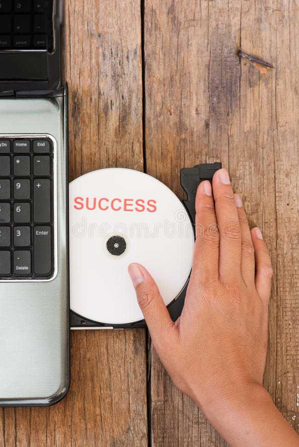 Success concept with compact disk laptop on wood b stock images