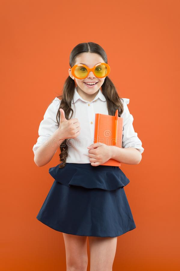 Success concept. happy school girl in uniform and party glasses. small child with notebook. literature lesson education. Writing in workbook. children stock photography