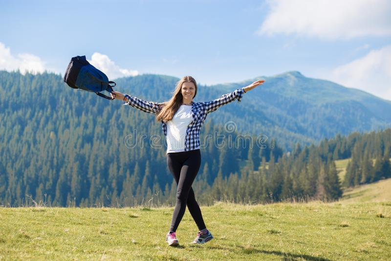 Success concept. Hiker woman cheering elated and blissful with arms raised in sky after hiking to mountain. Top stock images