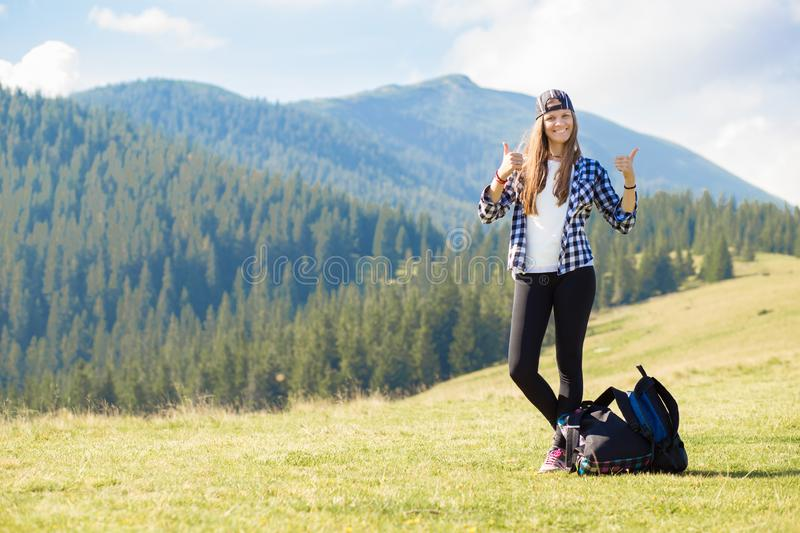 Success concept. Hiker woman cheering elated and blissful with arms raised in sky after hiking to mountain stock image