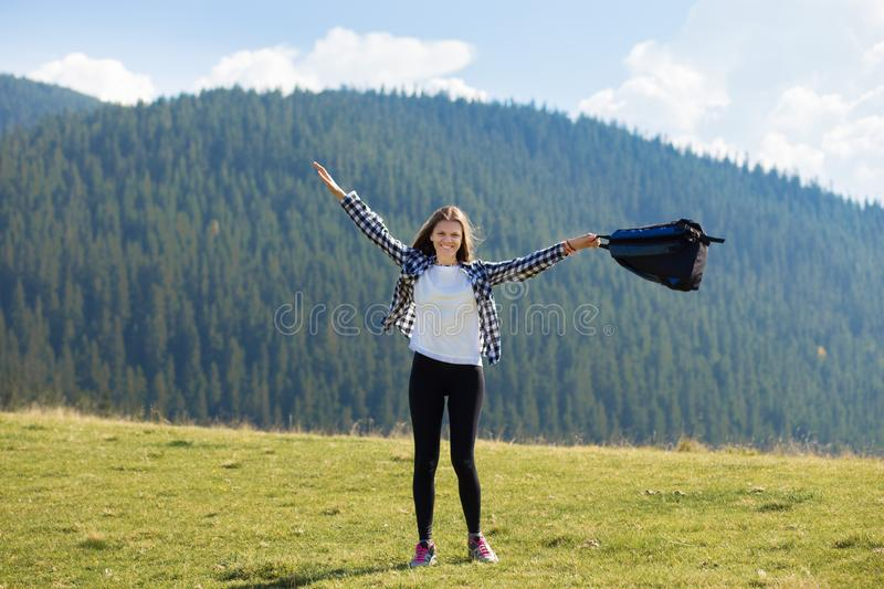 Success concept. Hiker woman cheering elated and blissful with arms raised in sky after hiking to mountain. Top stock photo