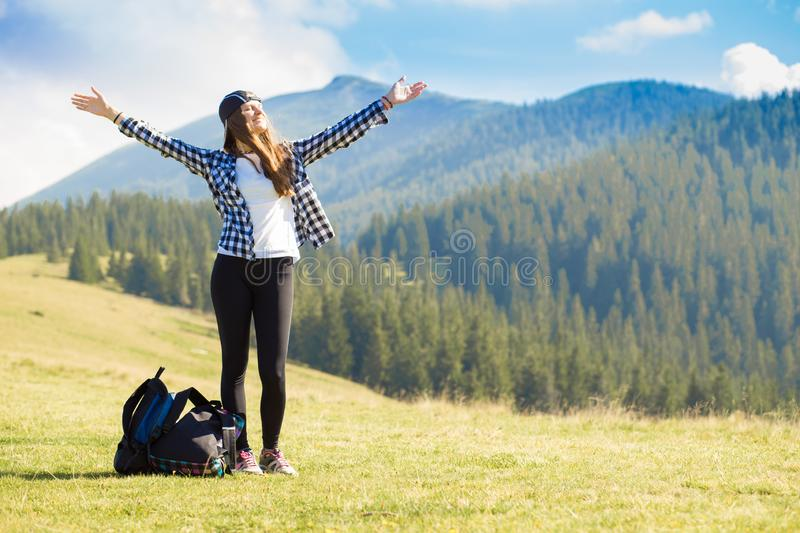 Success concept. Hiker woman cheering elated and blissful with arms raised in sky after hiking to mountain. Top royalty free stock photo