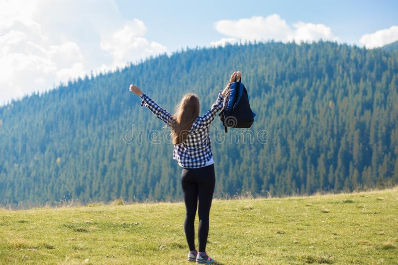 Hiker woman cheering elated and blissful with arms raised in sky after hiking to mountain top. Success concept. Hiker woman cheering elated and blissful with stock photo