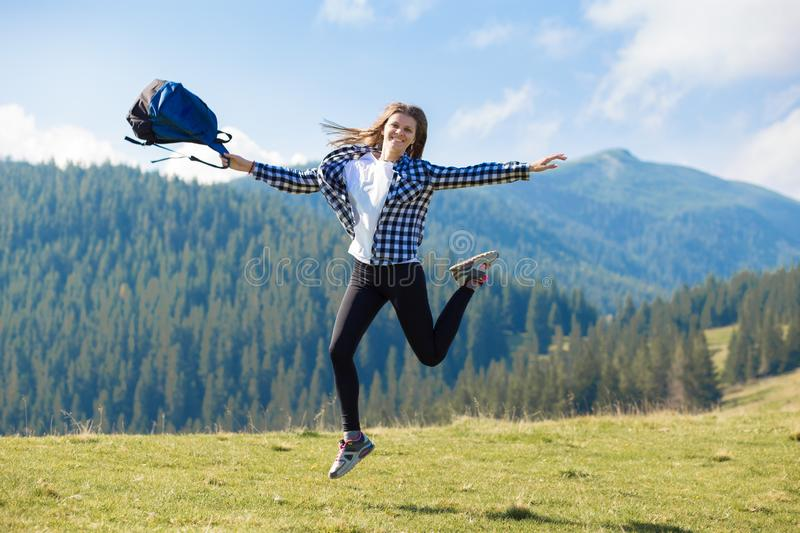Hiker woman cheering elated and blissful with arms raised in sky after hiking to mountain top. Success concept. Hiker woman cheering elated and blissful with royalty free stock photos