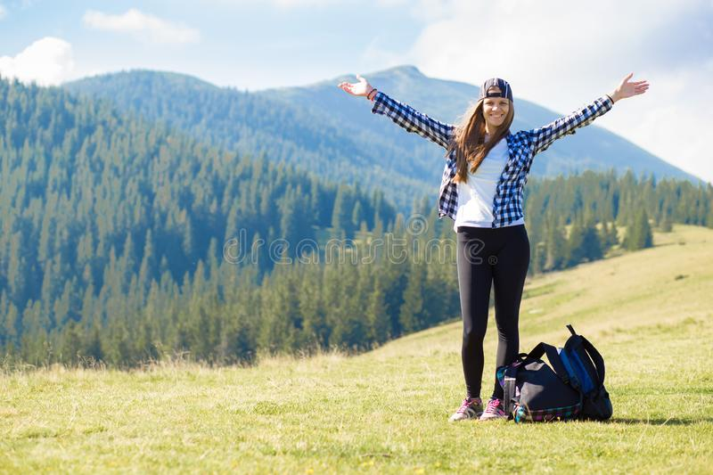 Hiker woman cheering elated and blissful with arms raised in sky after hiking to mountain top. Success concept. Hiker woman cheering elated and blissful with stock photos