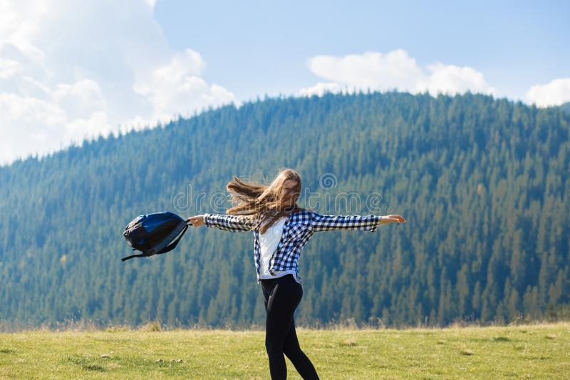 Hiker woman cheering elated and blissful with arms raised in sky after hiking to mountain top. Success concept. Hiker woman cheering elated and blissful with royalty free stock image
