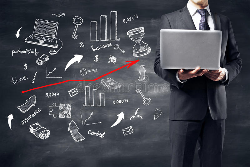 Success concept. Man using laptop on blackboard background with creative business sketch. Success concept stock photos