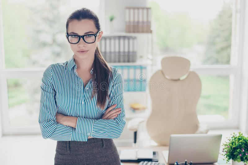 Success concept. Portrait of serious young business lady in glasses and with ponytail, standing at her office in strict outfit stock photo