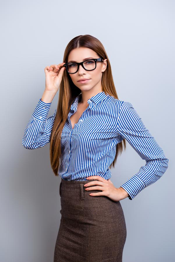 Success concept. Portrait of serious young business lady in glasses and formal wear, standing at thepure background royalty free stock photography