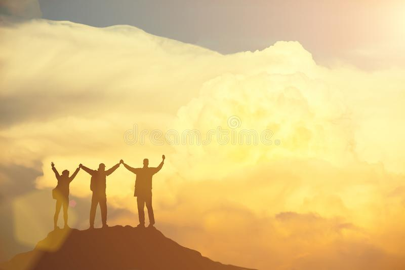 Success concept. Silhouetted of group of people raised hand up in the sky with happy. stock photography