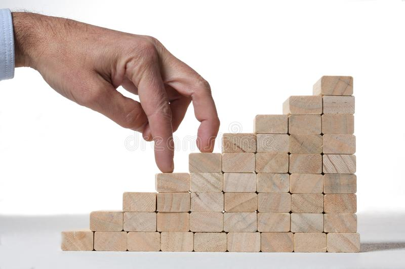 Success concept:stairs build with toy wooden blocks and two human finger climbing it on white background. Stairs build with toy wooden blocks and two human royalty free stock image