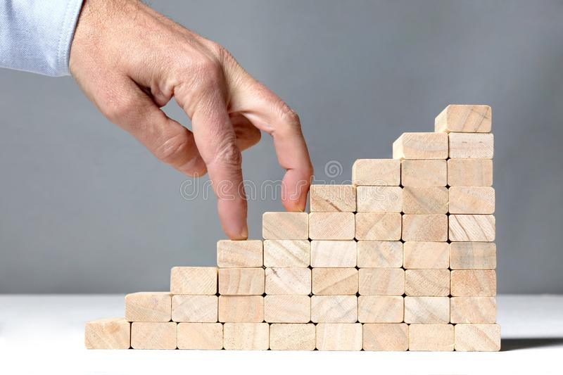 Success concept:stairs build with toy wooden blocks and two human finger climbing it on white background. Stairs build with toy wooden blocks and two human stock images
