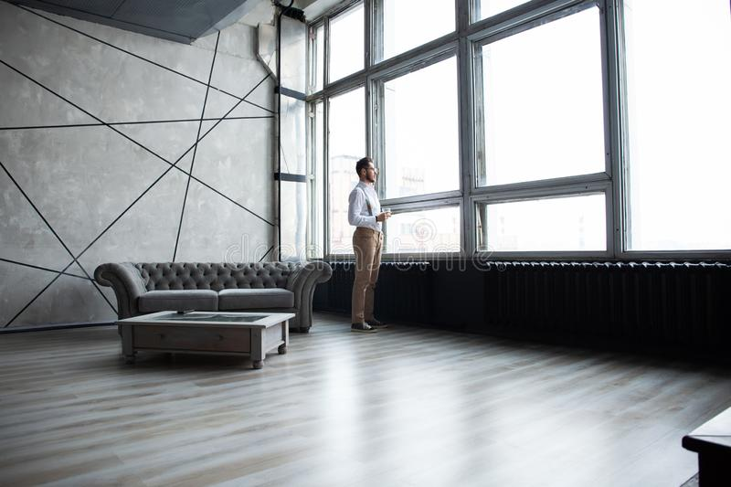 Success concept. Stylish young bearded man is standing near the window and looking far. He is in a suit, pensive and. Concentrated stock image