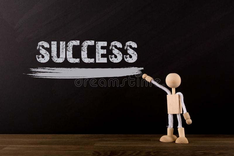 Success concept, Wooden Stick Figure pointing the word Success on a chalkboard royalty free stock photography