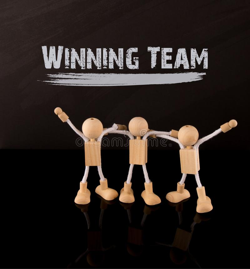 Success concept, Wooden Stick Figures team the word Winning Team on a chalkboard. royalty free stock image