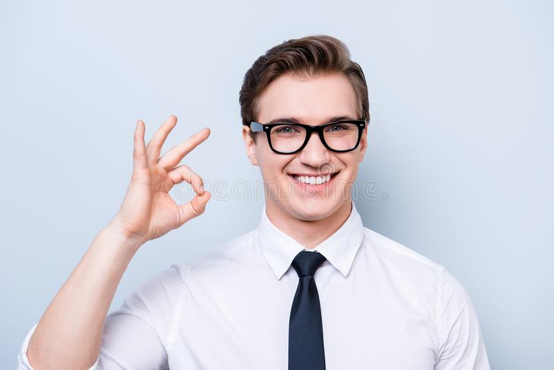 Success concept. Young handsome geek in a formal wear, black glasses, stands on pure light background, gesturing ok sign royalty free stock photos