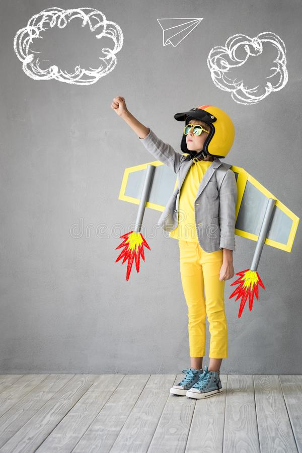 Success, creative and idea concept. Happy child playing with toy jetpack. Kid pilot ready to fly. Success, innovation and leader concept royalty free stock image
