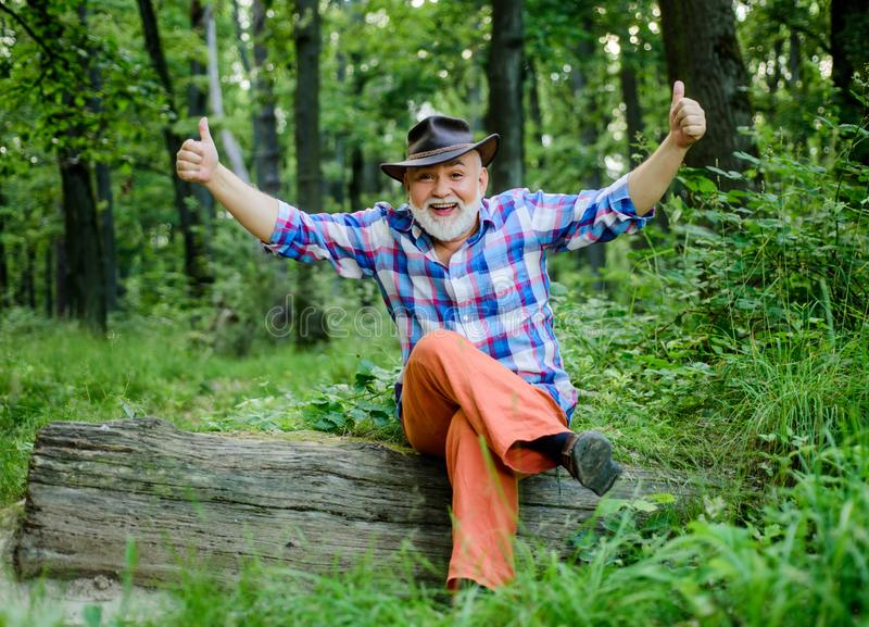 Success. farmer sit on wood. happy forester. human and nature. hiking in deep wood. forest owner. summer or spring royalty free stock image