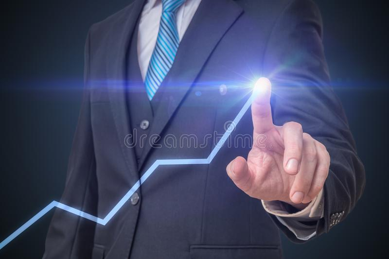 Success and growth in business concept. Businessman is drawing increasing graph with finger royalty free stock photography