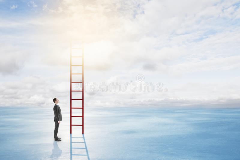 Success and growth concept. Thoughtful young businessman climbing ladder on bright sky with clouds background. Success and growth concept royalty free stock photo