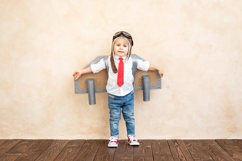 Success, imagination and innovation technology concept. Funny kid with toy jet pack. Happy child playing at home. Success, imagination and innovation technology stock photography