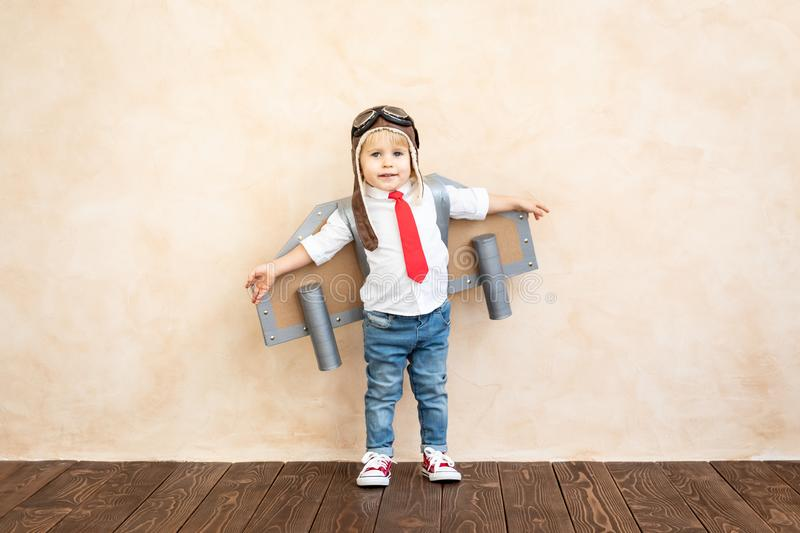 Success, imagination and innovation technology concept. Funny kid with toy jet pack. Happy child playing at home. Success, imagination and innovation technology stock photos