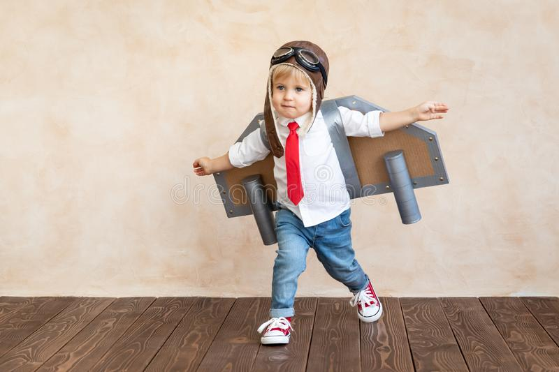 Success, imagination and innovation technology concept. Funny kid with toy jet pack. Happy child playing at home. Success, imagination and innovation technology royalty free stock image