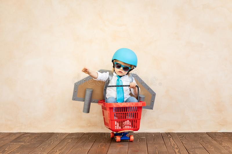 Success, imagination and innovation technology concept. Funny kid with toy jet pack. Happy child playing at home. Success, imagination and innovation technology stock images