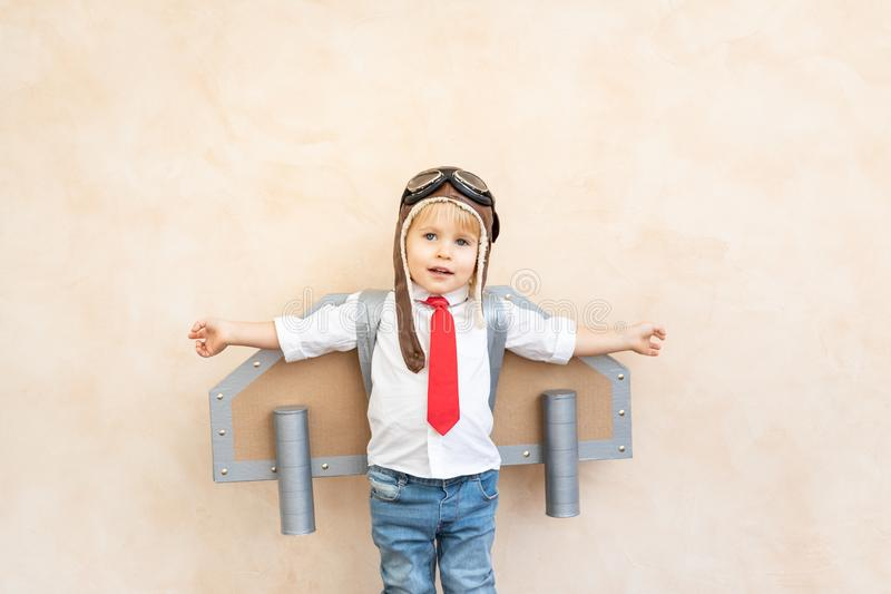 Success, imagination and innovation technology concept. Funny kid with toy jet pack. Happy child playing at home. Success, imagination and innovation technology royalty free stock photography