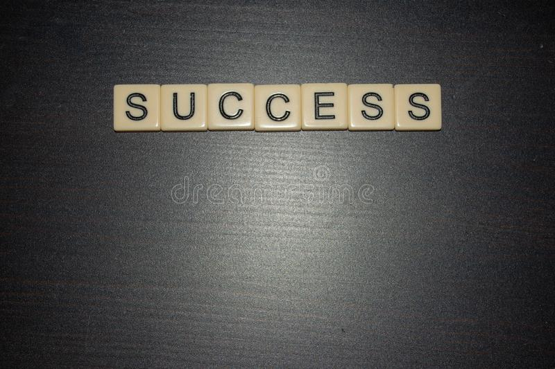 Success letter tiles lined up on a black background. Work together, find success in life, business, education. Open concept. Space. Success letter tiles lined up stock image