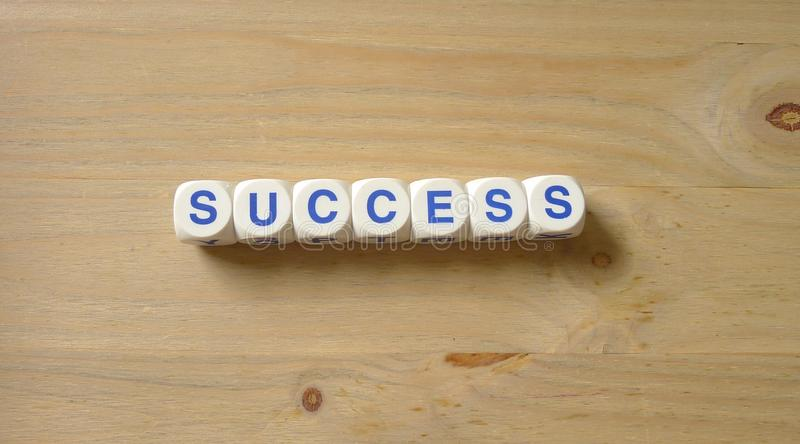 Success. Letters cube wordings on wood background royalty free stock images
